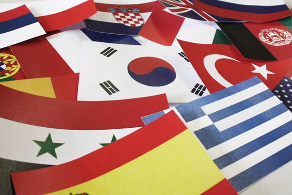 Flags from many different countries, which are lying next to each other on a table