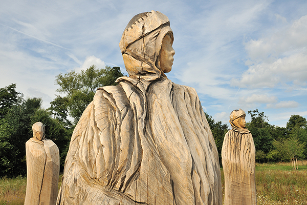 three large wooden figures in the countryside