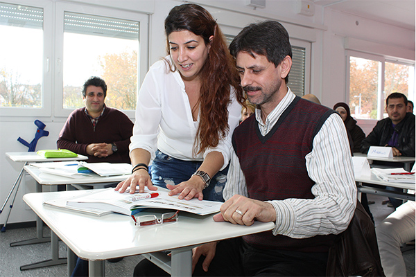 a woman, next to a man, in a classroom, who is looking at a text book with the man